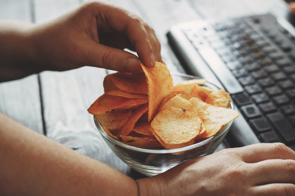 woman working at computer and eating chips
