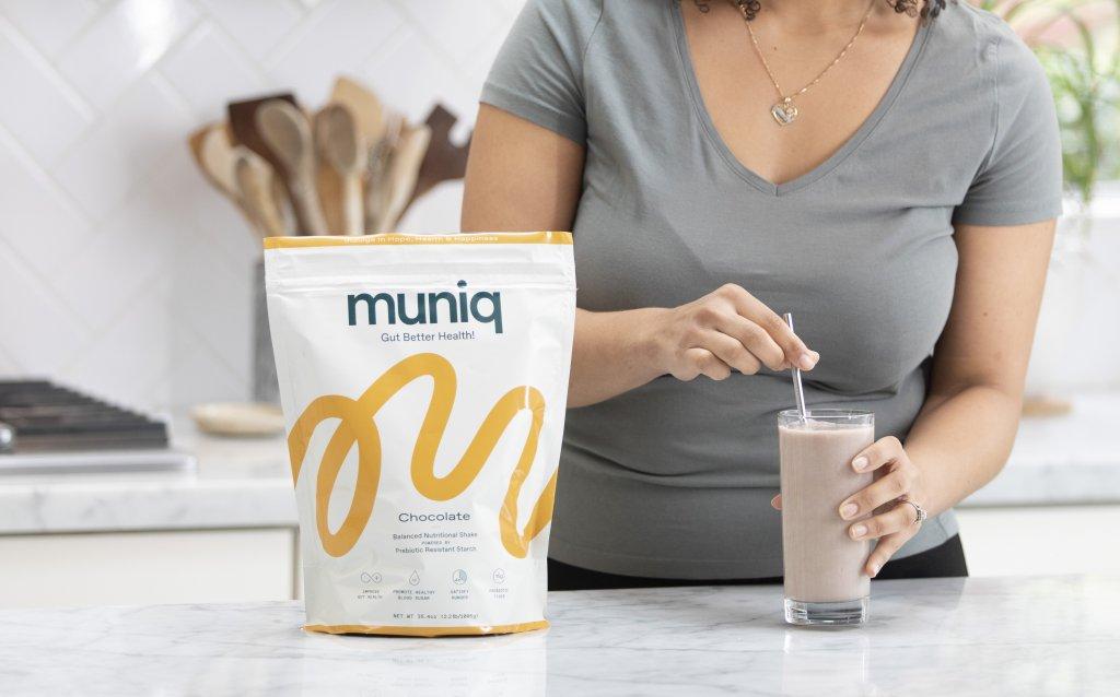 A woman mixing a muniq shake in her glass