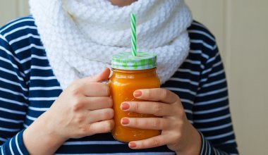 An image of a girl holding a carrot cake smoothie
