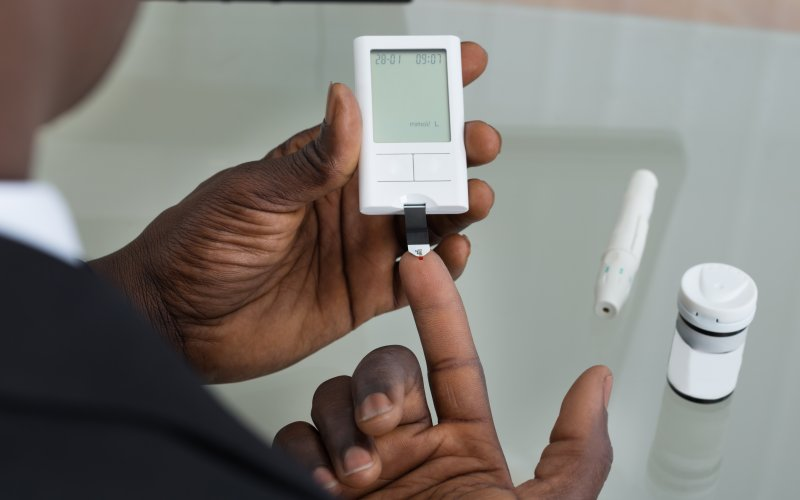 An image of someone taking a blood sugar reading