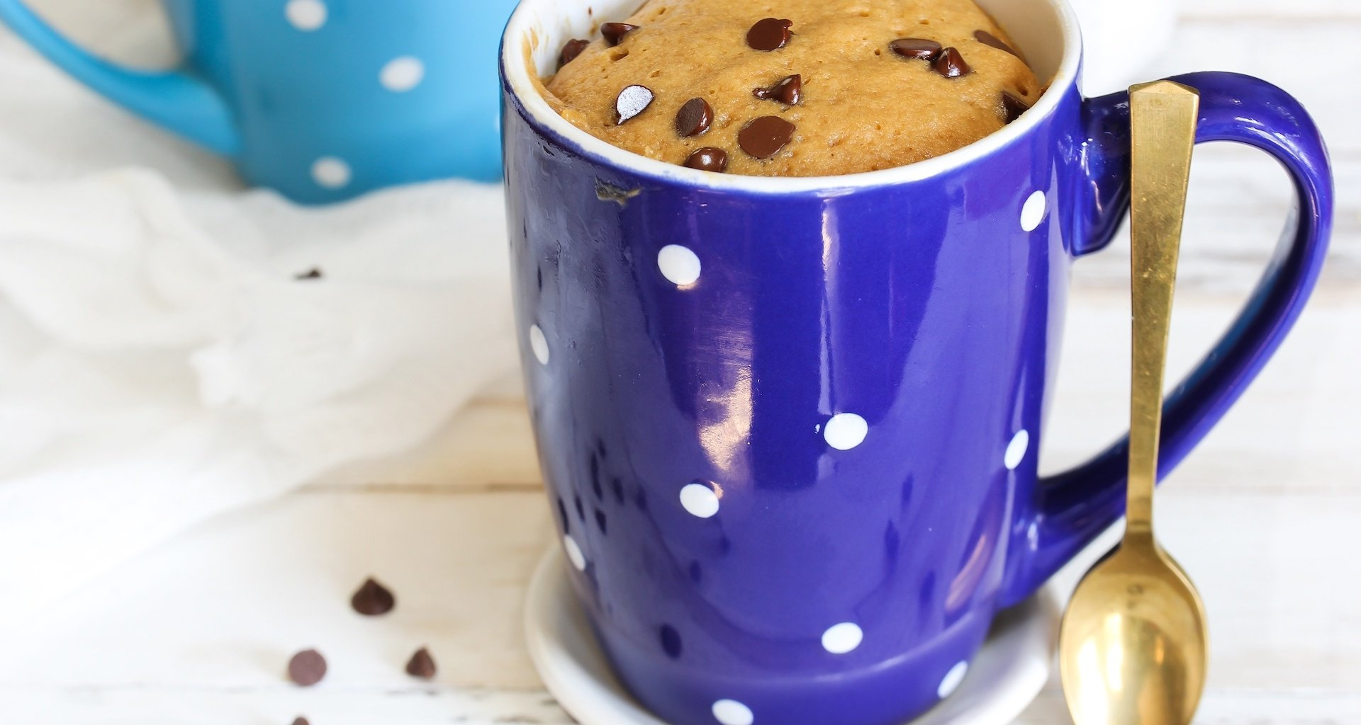 A picture of a blue mug with a microwaved cake inside